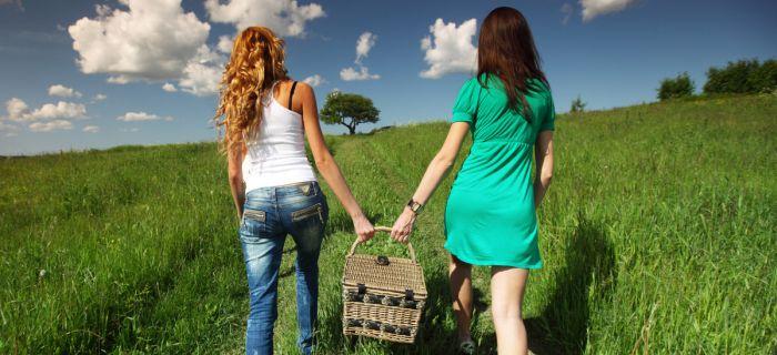 girlfriends on picnic in green grass field